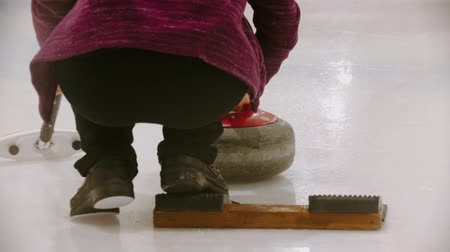 gránit : Curling - a young woman pushes off from the stand with granite stone on the ice rink