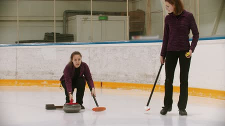 gránit : Curling - two women having a curling training on the ice rink