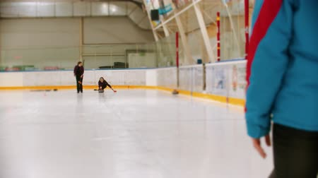 dois objetos : Curling training - two women having a curling training on the ice rink Stock Footage