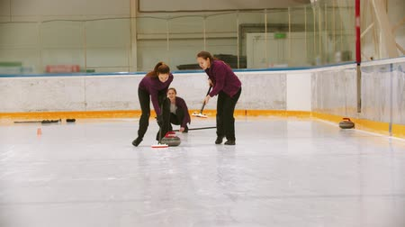 gránit : Curling training - leading granite stone on the ice - rubbing the ice before the stone Stock mozgókép