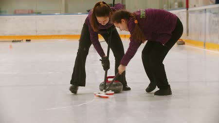 gránit : Curling training indoors - leading granite stone on the ice - rubbing the ice before the stone