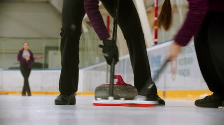 лучше : Curling training indoors - leading granite stone on the ice - rubbing the ice before the stone for better glide