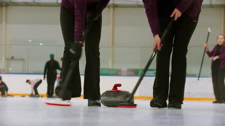 gránit : Curling training indoors - leading granite stone on the ice - two women rubbing the ice before the stone Stock mozgókép