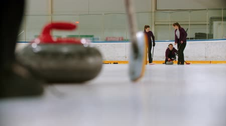 gránit : Curling training indoors - leading granite stone on the ice - two young women rubbing the ice before the stone