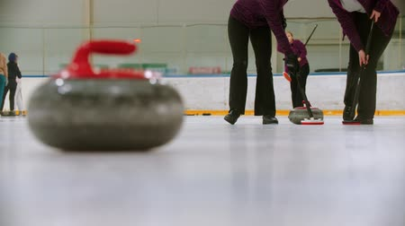 gránit : Curling training - leading granite stone on the ice - two women rubbing the ice before the stone
