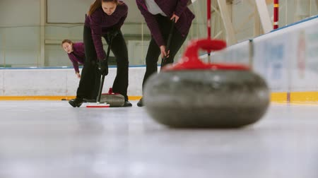 gránit : Curling training - leading granite stone on the ice - two women rubbing the ice before the stone - kicking others hostile stone from the point