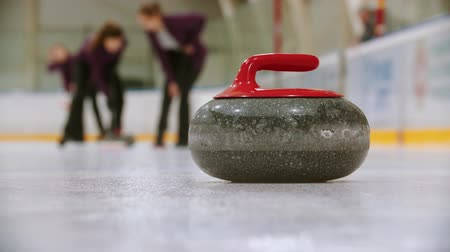 gránit : Curling training - leading granite stone on the ice - two women rubbing the ice before the stone to move others hostile stone from the point Stock mozgókép