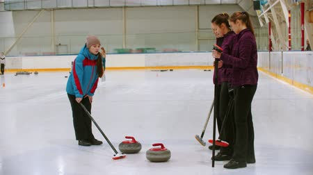 gránit : Curling training - the judge measuring the distance between two stones on the ice Stock mozgókép
