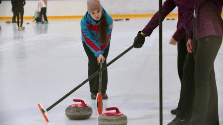 gránit : Curling training indoors - the judge measuring the distance between two stones on the ice