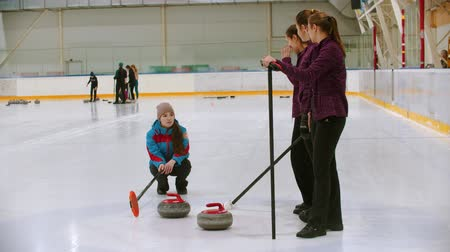 gránit : Curling training - the judge measuring the distance between two stones on the ice rink Stock mozgókép