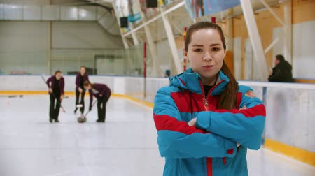 gránit : Curling training - the judge in blue jacket standing on the ice rink looking in the camera - her students playing curling on the background