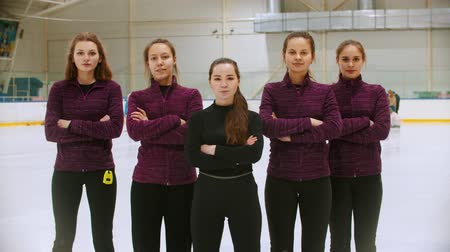gránit : Curling training - the judge standing on the ice rink with her women students - their hands crossed on the chest