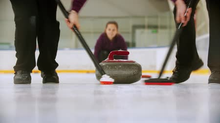 gránit : Curling - leading granite stone on the ice and rubbing the ice before the stone