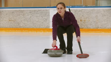 fegyelem : Curling training on ice rink - a young woman pushing the stone on the rink with a brush