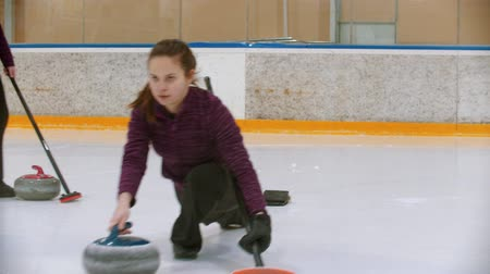 bodorítás : Curling training on ice rink - a young woman pushes off from the stand with a stone biter Stock mozgókép