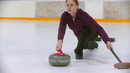 gránit : Curling training - a young woman pushes off from the stand with a stone biter Stock mozgókép