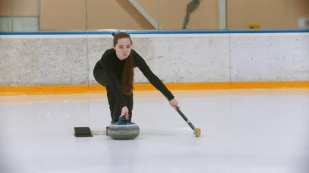 ondulação : Curling training - a young woman with long hair pushes off from the stand with a stone biter