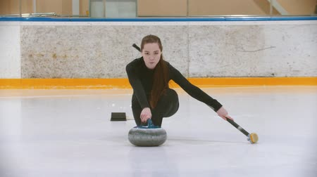gránit : Curling training - a young woman with long hair pushes off from the stand - leading the stone biter Stock mozgókép