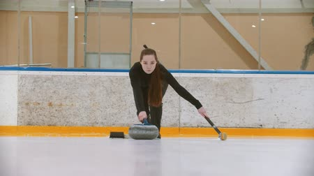 curling hair : Curling training - a young woman with long hair pushes off from the stand - leading the stone biter with blue handle