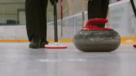 fegyelem : Curling training on the ice rink- a granite stone biter with red handle hitting another biter of opposite team