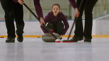 gránit : Curling training - rubbing the ice before the biter - third woman watching other players Stock mozgókép
