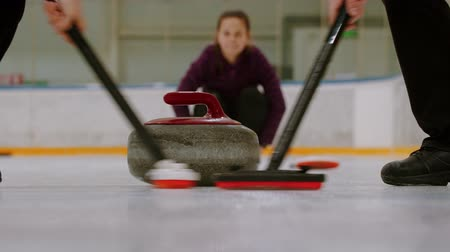gránit : Curling training - rubbing the ice before the biter with red handle - third woman watching other players