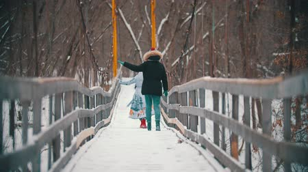 Two young women walking on the snowy bridge