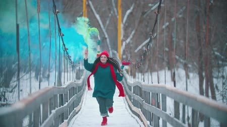 Two young happy women running on the snowy bridge holding colorful smoke bombs