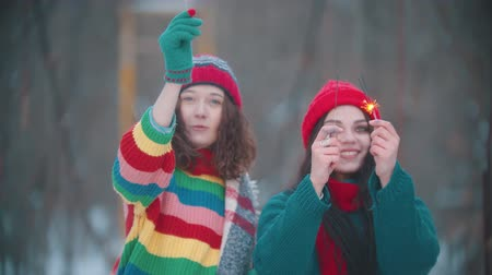 požár : Two young smiling women playing at winter with lighted up sparklers and looking into camera