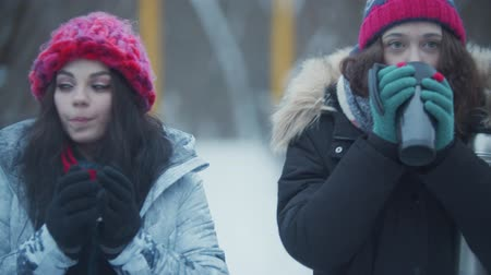 Two young beautiful women friends walking on the snowy bridge and drinking hot drinks from the thermos