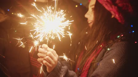 požár : Two young women friends playing with sparklers at night and singing a song - looking in the camera