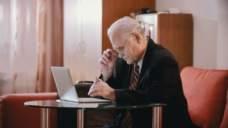 zmarszczki : Elderly grandfather - grandfather in a jacket and tie is slowly typing on a computer
