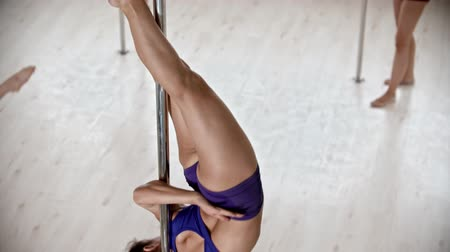A woman trainer showing her students a pole dancing trick - other about to repeat it
