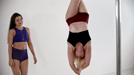 A blonde woman having a pole dancing training in the white studio - her trainer helping her to keep the balance upside down Stock Footage