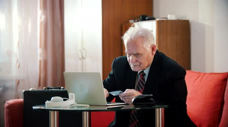 задумчивый : Elderly grandfather - old grandfather is entering bank card number into laptop