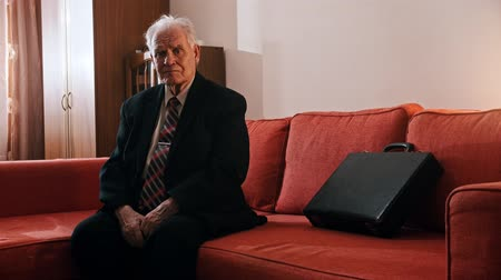 Elderly grandfather - grandfather is sitting on a sofa with a suitcase and touching a hand over his face