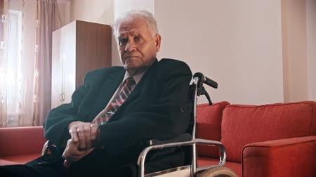 Elderly grandfather - grandfather is sitting in a wheelchair and looking at the camera