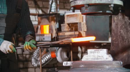 chamas : Blacksmith working - putting a longer piece of metal under the pressure of industrial forging machine Vídeos
