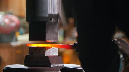 chamas : Forging an object out of hot metal using an industrial pressure machine Vídeos