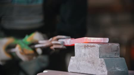 Forging an item out of hot longer piece of metal using a pressure machine