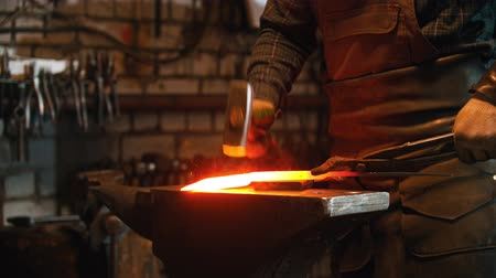chamas : Blacksmith working - man heating up the longer piece of metal in the furnace and hitting it with a hammer Vídeos