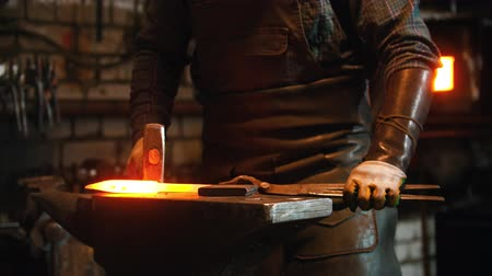 хит : Blacksmith working in the workshop - man heating up the longer piece of metal in the furnace and hitting it with a hammer