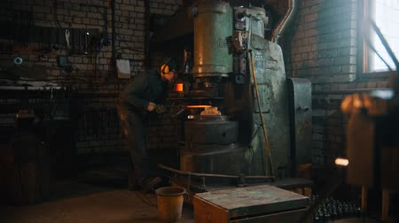 chamas : Forging industry - a man blacksmith working with big industrial pressure machine in a workshop