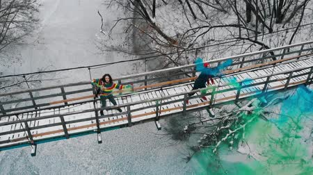 patlayıcı : Two women on the snowy bridge having fun with green and blue smoke bombs