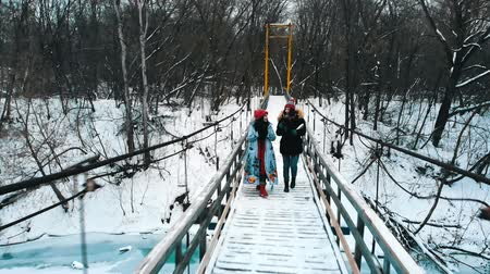 друг : Two young women drinking hot drinks and walk on the bridge Стоковые видеозаписи