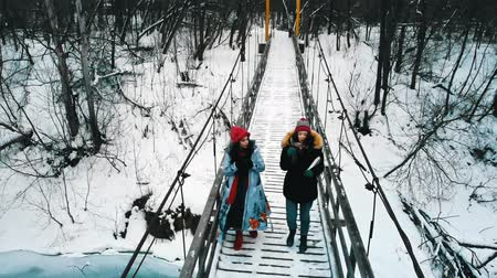 ormanda yaşayan : Two young women friends drinking hot drinks from the thermos on the snowy bridge in winter forest
