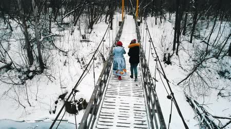 друг : Two women friends drinking hot drinks from the bottle on the snowy bridge in winter forest