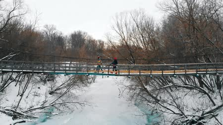 Two colorful women friends walking on the snowy bridge