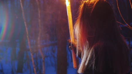Young scared woman with torch searching a way out in the dark forest Stockvideo
