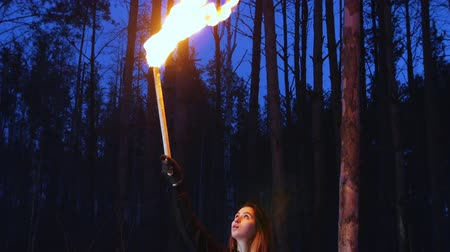 atmosféra : A woman overhead waving with torch standing in winter forest